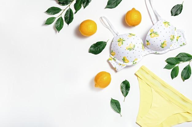 Lingerie de algodão de garota verão com limões em fundo branco, copie o espaço. camada plana, vista superior. conceito de moda de verão