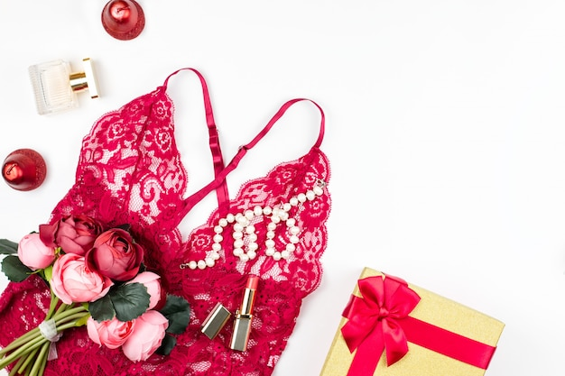 Lingerie de renda vermelha mulheres com giftbox, flores, compõem itens sobre fundo branco. cartão postal para o dia das mulheres.