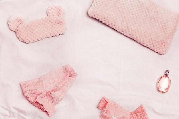 Lingerie e perfume feminino elegante, calcinha de renda de mulher e sutiã, travesseiro e máscara de olho fofa para dormir no lençol branco. vista de cima.