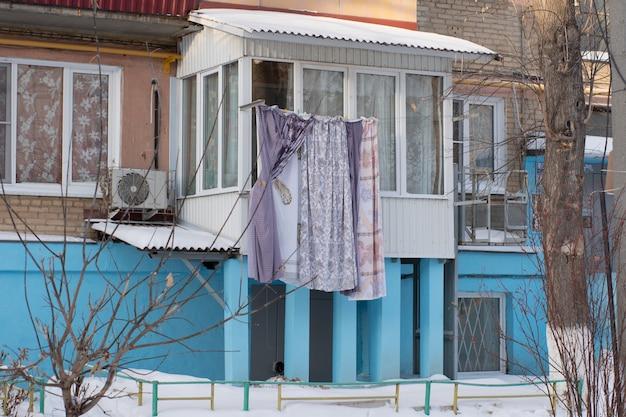 Lingerie seca no inverno em uma corda na rua, uma casa azul, arbustos.