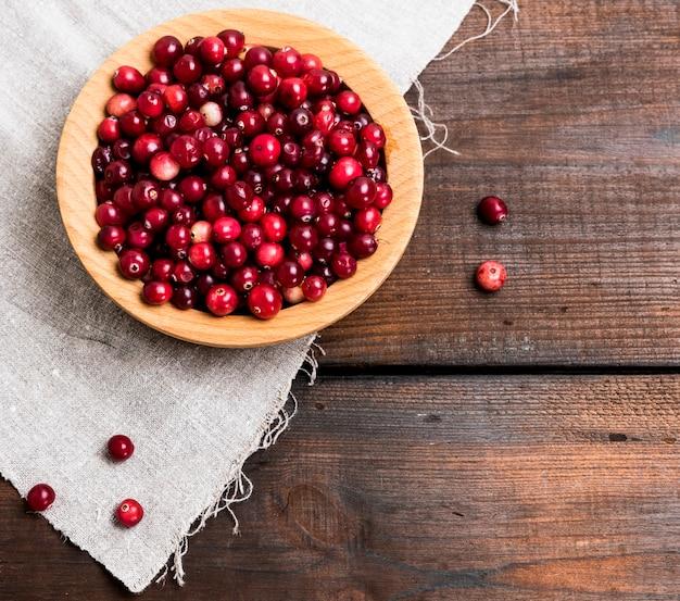 Lingonberries vermelhos maduros em uma tigela de madeira redonda