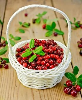 Lingonberry com folhas em uma cesta de vime branco, galhos com folhas e mirtilos vermelhos maduros contra uma placa de madeira