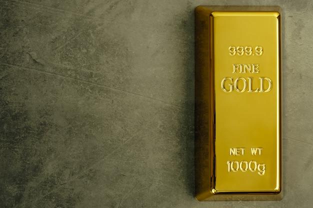 Lingote de ouro puro metal ouro sobre uma textura cinza.