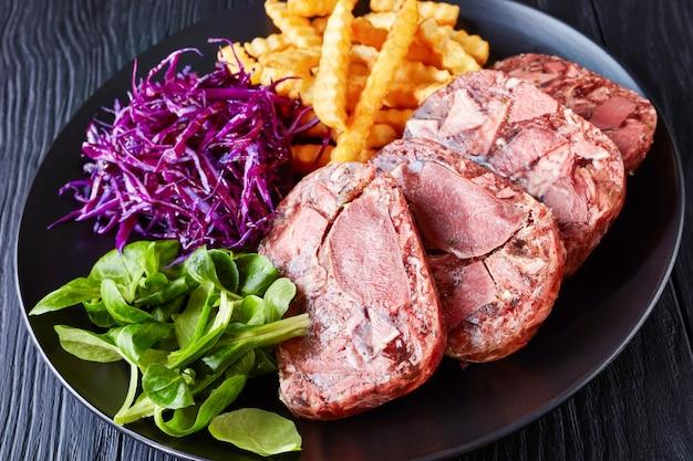 Língua de boi fatiada e gelatina de carne servida com batatas fritas, folhas verdes e salada de repolho roxo em uma placa preta sobre uma mesa de madeira, vista de cima, close-up