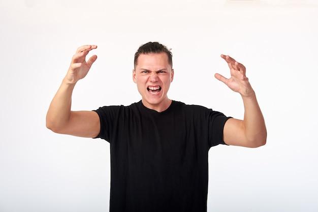 Linguagem corporal. dominação masculina. bravo agressivo jovem infeliz em camisa total gritando. estúdio disparado em fundo branco.