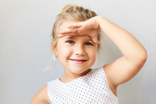 Linguagem corporal. foto horizontal de uma menina alegre e fofa com cabelo louro recolhido, segurando a palma da mão na testa como se estivesse olhando para longe, tentando ver algo ao longe, sorrindo alegremente