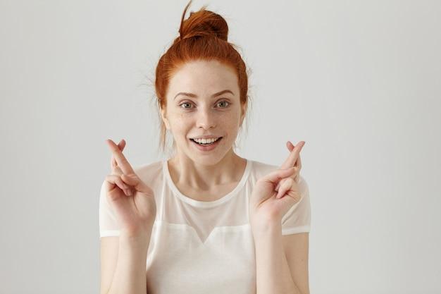 Linguagem corporal. garota adolescente supersticiosa com cabelo ruivo e rosto bonito cruzando os dedos para dar sorte, esperando que seus desejos se tornem realidade, tendo um olhar feliz animado. emoções e sentimentos humanos