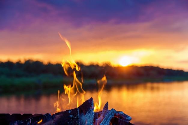 Línguas de chamas vermelhas do fogo perto do rio ao pôr do sol.