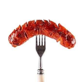 Linguiça assada no garfo isolado no fundo branco.