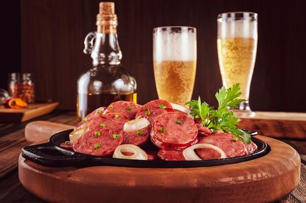 Linguiça calabresa defumada fatiada com cebola e cerveja - petisco brasileiro