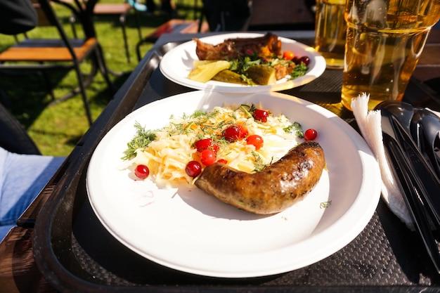 Linguiça com salada no prato e cerveja light na bandeja de comida de rua
