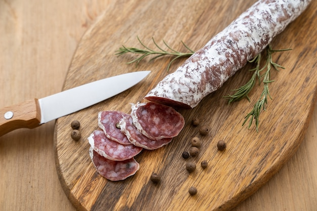 Linguiça crua defumada cortada em pedaços e uma faca em uma tábua de madeira