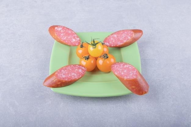 Linguiça defumada e tomate cereja na placa verde.