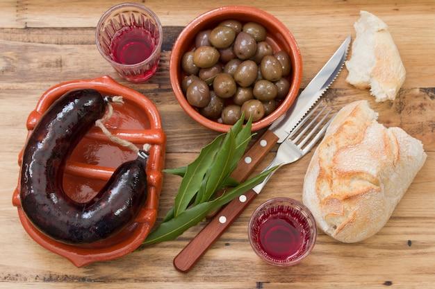 Linguiça defumada em prato de cerâmica com azeitonas, pão e vinho