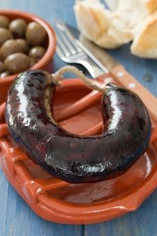 Linguiça defumada no prato típico português de cerâmica e azeitonas