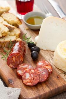 Linguiça defumada, queijo, pão e copo de vinho tinto