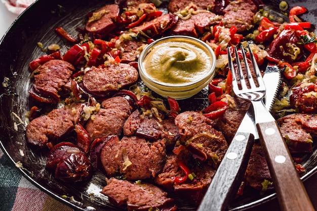 Linguiça fatiada e mistura de legumes frescos fritos na panela rústica com mostarda no pano de prato.