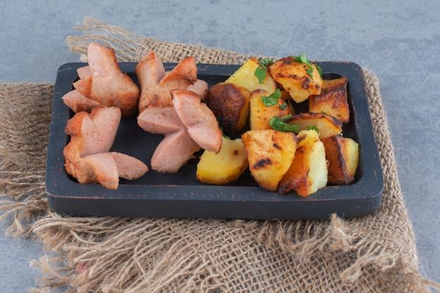 Linguiça frita e batata na placa de madeira preta.