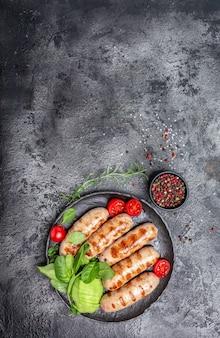Linguiça grelhada com espinafre, abacate e tomate cereja. prato de churrasco quente. menu de dieta paleo keto. imagem vertical. vista do topo. lugar para texto.