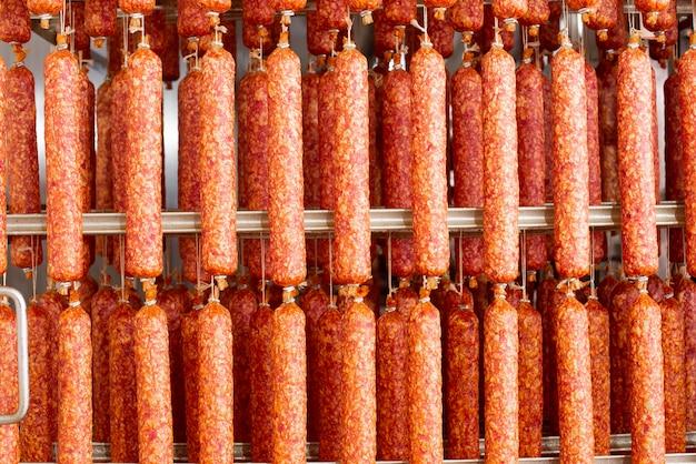 Linguiça seca pendurado na corda na armação de metal na casa de fumaça