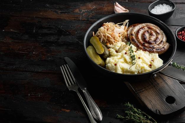 Linguiças alemãs tradicionais com purê de batata e chucrute em frigideira de ferro fundido