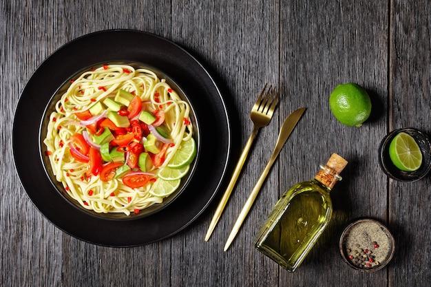 Linguine com abacate, tomate e limão polvilhado com pimenta picada e cebola roxa em uma tigela preta sobre uma mesa de madeira, vista horizontal de cima, camada plana