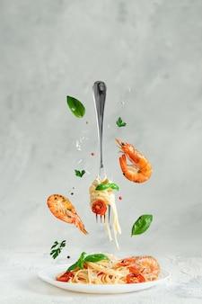 Linguine de macarrão com camarão e garfo voando sobre o prato. ainda vida criativa. conceito de comida italiana