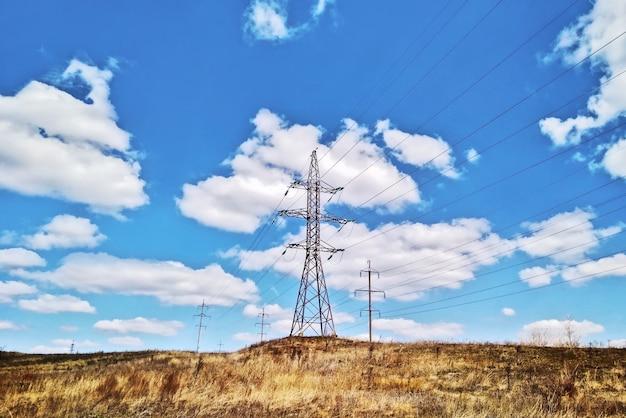 Linha aérea de energia em dia de verão no campo no fundo do céu azul
