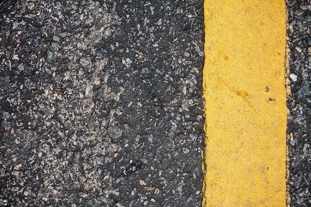 Linha amarela na textura da estrada