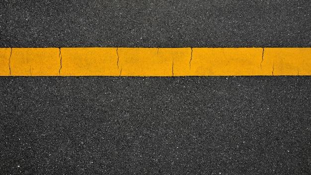 Linha amarela no fundo de estrada de asfalto