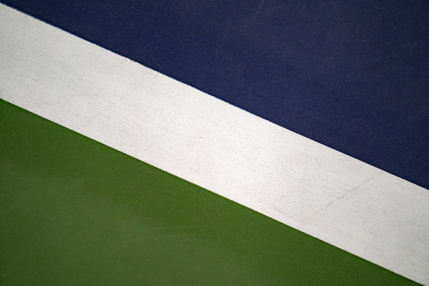 Linha branca diagonal no campo de ténis azul e verde, textura para o fundo