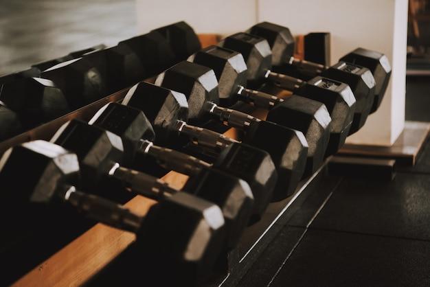 Linha com halteres pretos é deitado na prateleira no ginásio