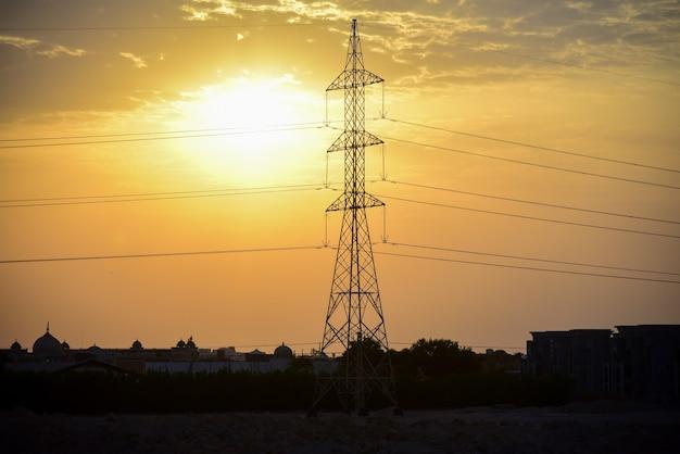 Linha de alta tensão ao pôr do sol em um país árabe.