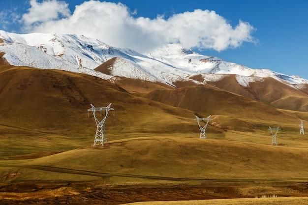 Linha de alta tensão no quirguistão. postes de eletricidade de tensão nas montanhas