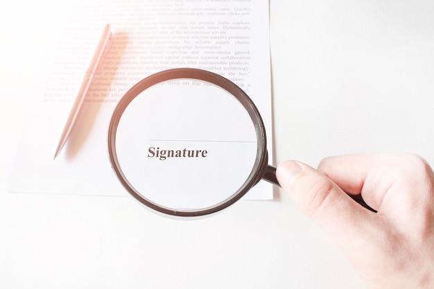 Linha de assinatura em contrato com caneta e lupa