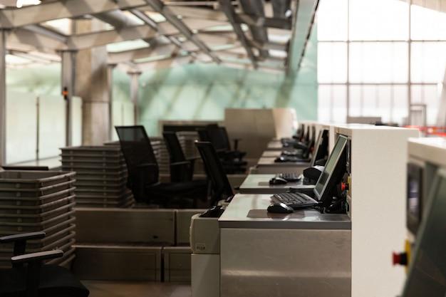 Linha de balcões de check-in com monitores de computador no terminal do aeroporto vazio devido a pandemia de coronavírus / surto de covid-19.