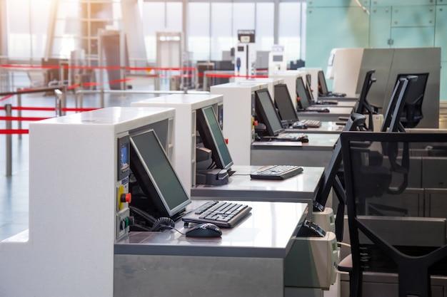 Linha de balcões de check-in vazios com monitores de computador no aeroporto.