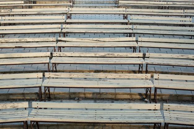 Linha de bancos de madeira no teatro de verão em um parque da cidade.