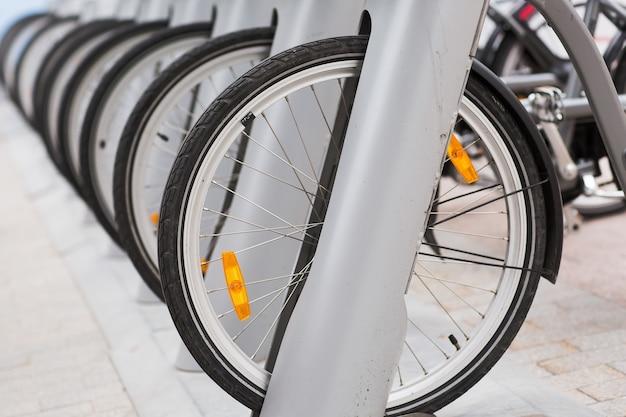 Linha de bicicletas vintage estacionadas para alugar na calçada.