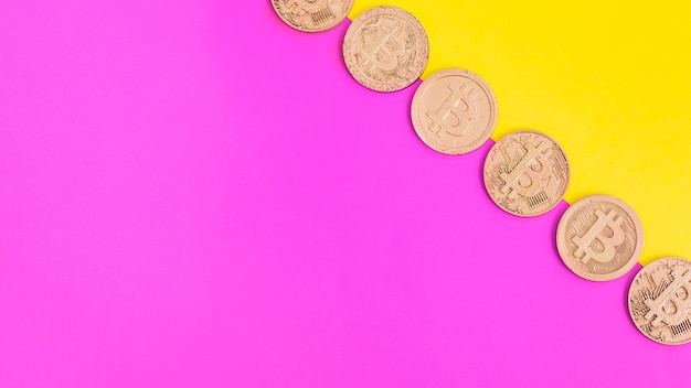 Linha de bitcoins sobre fundo duplo rosa e amarelo