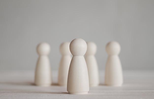 Linha de bonecos de madeira em pé na mesa de madeira que se destacam do grupo