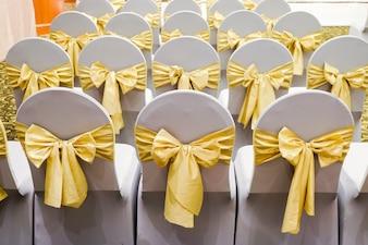Linha de cadeiras brancas decoradas com fitas de ouro