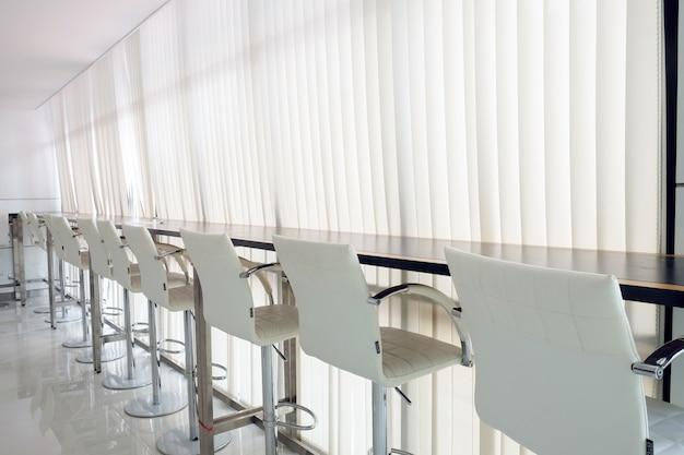 Linha de cadeiras de bar ou escritório com trilho de cortina branca e luz do sol