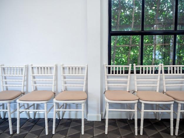 Linha de cadeiras de madeira vintage branco com almofadas.