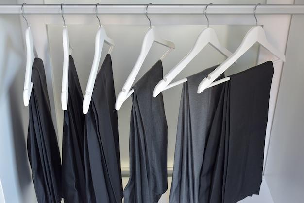 Linha de calça cinza e preta paira no guarda-roupa em casa