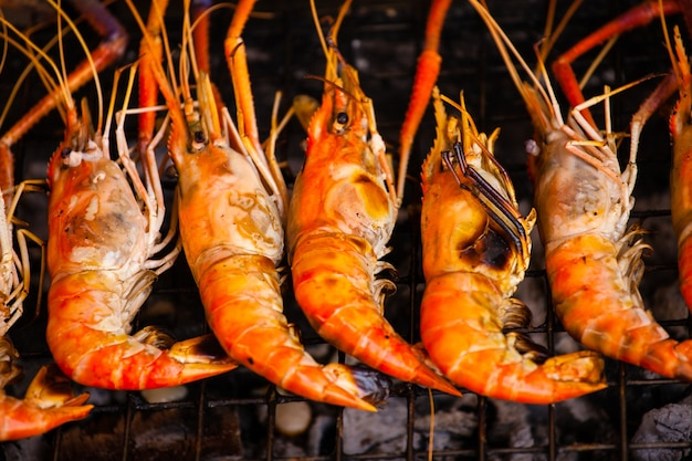 Linha de camarões grelhados coloridos em fogo quente.