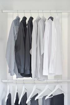 Linha de camisas brancas, cinza e pretas com calças penduradas no guarda-roupa de madeira