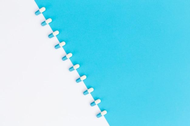 Linha de cápsulas dispostas em fundo duplo branco e azul