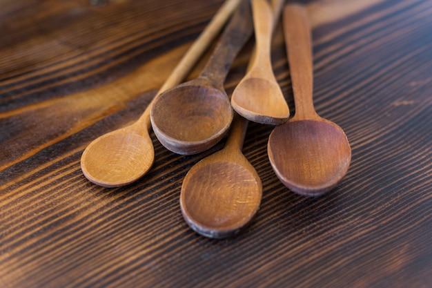 Linha de colheres de madeira velhas sortidas, deitado sobre uma superfície de madeira