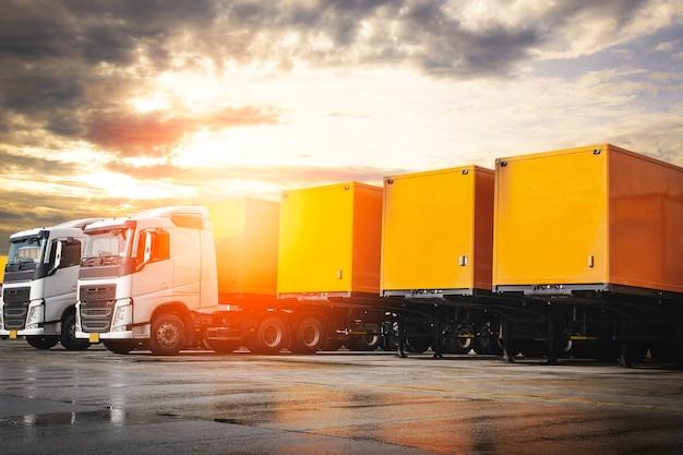 Linha de contêineres de caminhões de semirreboque e estacionamento na logística de caminhões de carga rodoviária da indústria de sunset sky